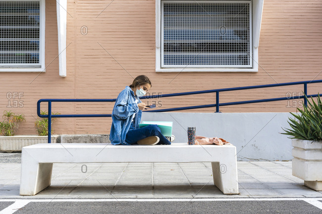Teenage girl taking picture of notes while sitting on concrete bench