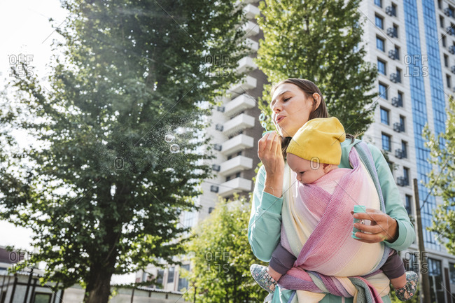 Mother carrying baby blowing bubble while standing on street in city
