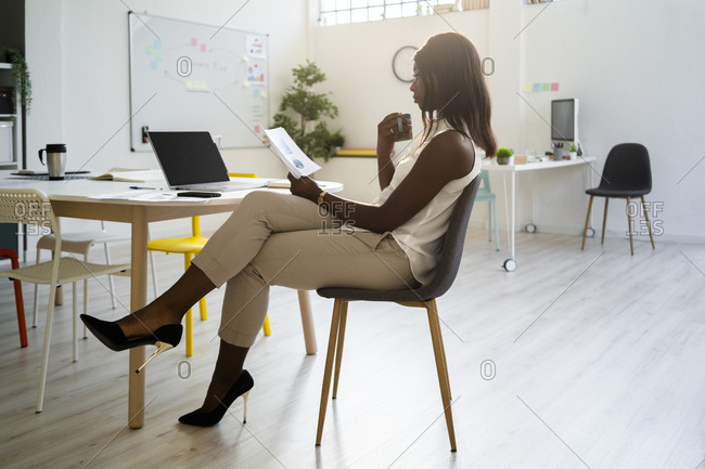 Woman with coffee cup reading paper while sitting on chair at office