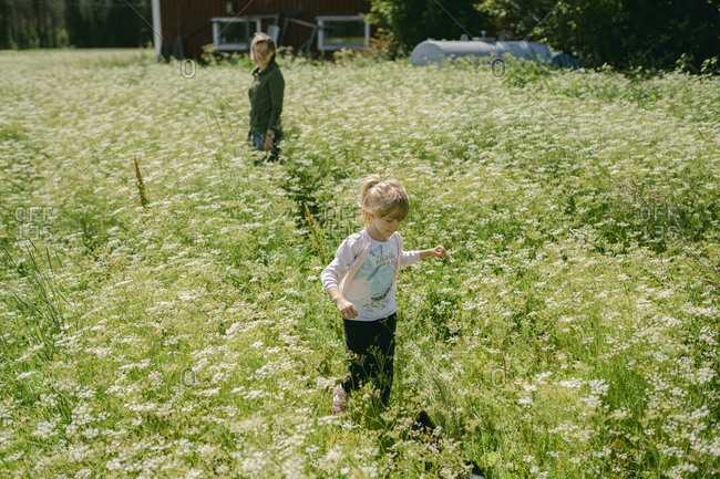 Daughter and mother spending leisure time on meadow during sunny day