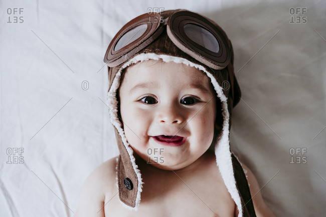 Cute male toddle wearing aviator cap while lying down on bed at home