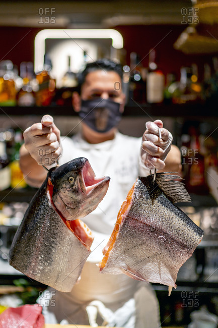 Male chef holding raw fish hanging on hooks in kitchen at restaurant