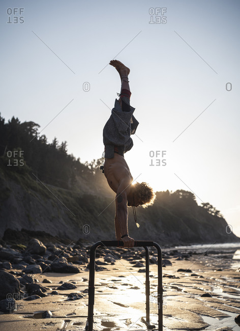 Young man practicing handstand on parallel bars at beach against sky