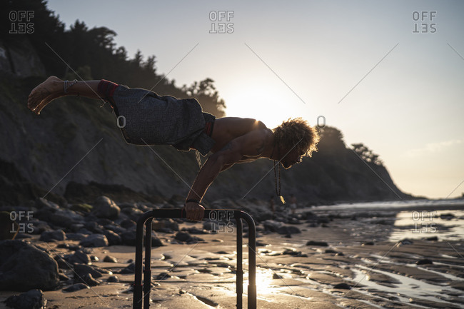 Shirtless young man exercising on parallel bars at beach against sky