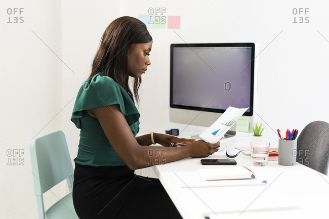Businesswoman analyzing graph paper while sitting by desk at office