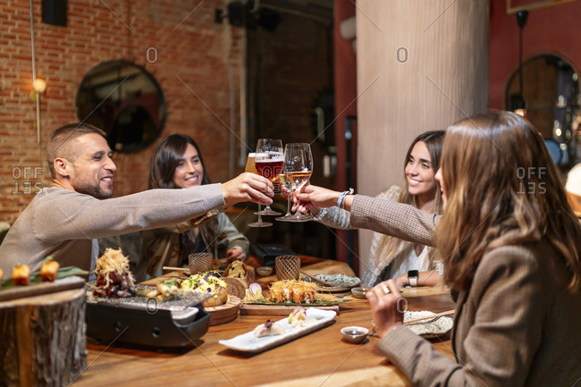Smiling friends toasting drink while sitting by table at restaurant