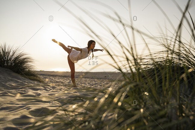 Flexible young woman practicing yoga on sand at beach during sunset
