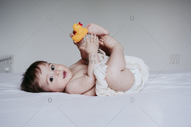Cute baby boy playing with duck toy while lying down on bed at home