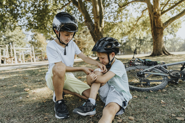 Boy putting bandage on younger brother knee sitting in public park