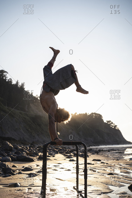Shirtless young man practicing handstand on parallel bars at beach