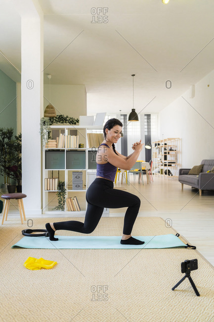 Young woman doing lunges exercise and recording on camera at home
