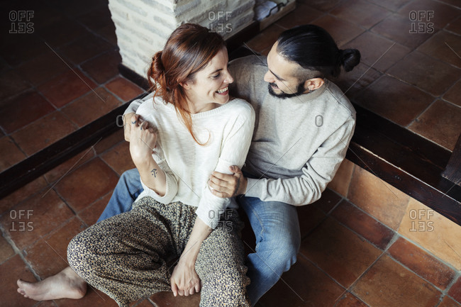 Happy couple looking at each other while sitting on floor at home