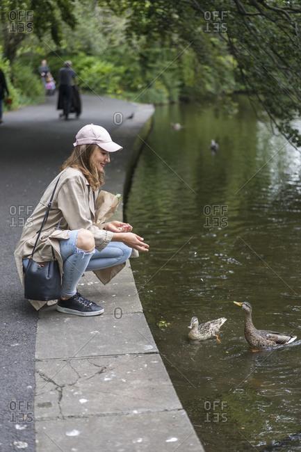 Young woman feeding dove bird in lake while crouching on sidewalk