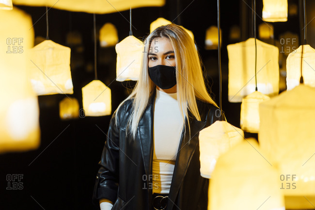 Young woman wearing protective face mask standing in between lamp
