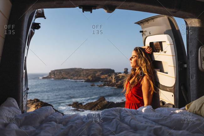 Young woman with hand in hair leaning on camper van door at beach