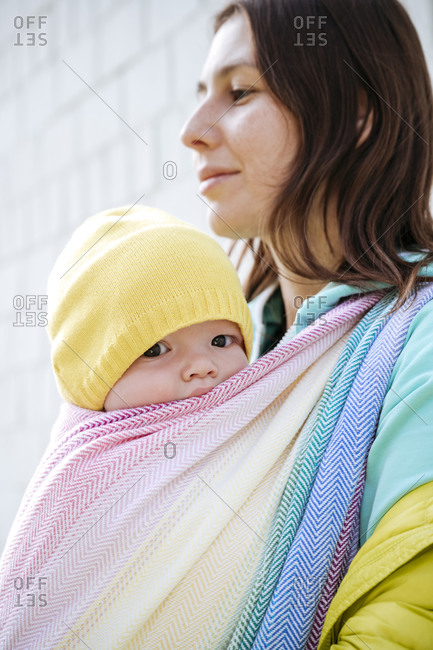 Mother holding baby wrapped in blanket looking away on sunny day