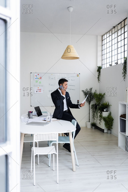 Businessman talking on phone while looking at document in office