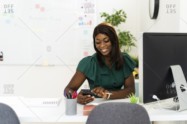 Smiling woman using mobile phone while sitting by desk at office