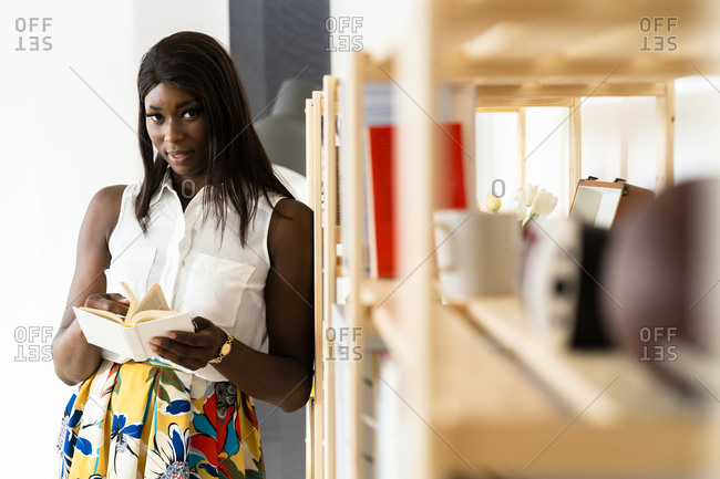 Businesswoman reading book while standing by bookshelf at office