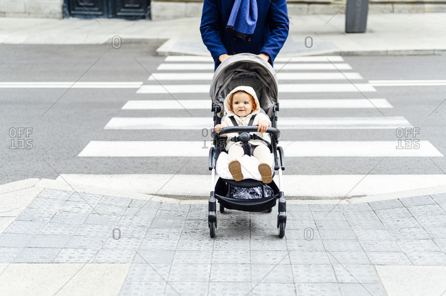 Man crossing road with baby boy sitting in baby stroller at city