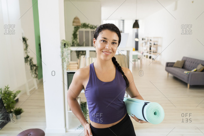 Young woman with hand on hip with exercise mat standing at home