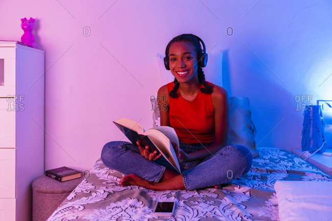 Smiling girl reading book with headphone sitting on bed at home