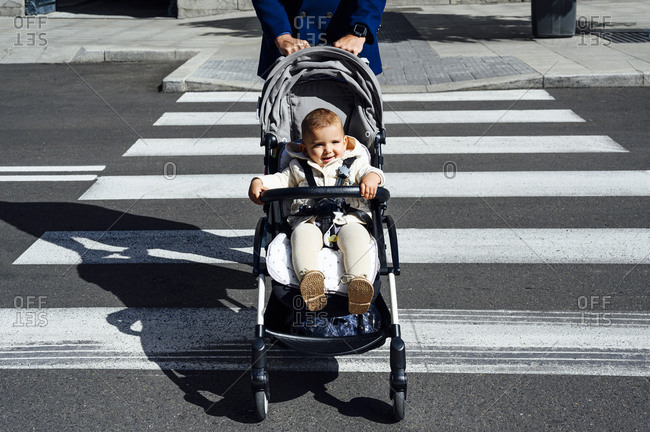 Father with smiling baby in baby stroller crossing road in city