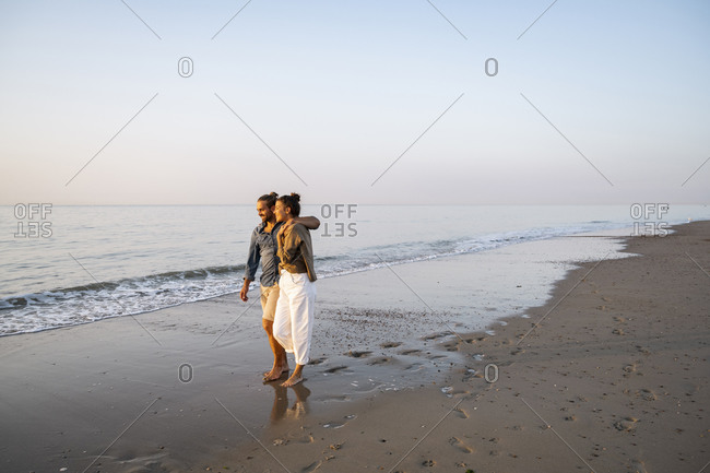 Smiling young couple enjoying sunset at beach against clear sky