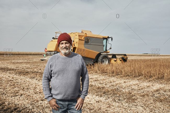 Smiling farmer standing against tractor harvesting crop at farm