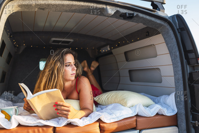 Woman with book looking away while lying in camper van at beach