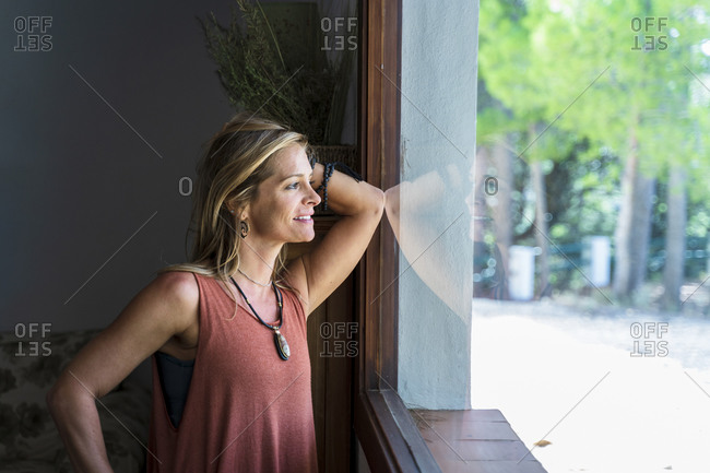 Thoughtful blond woman looking through window at health retreat
