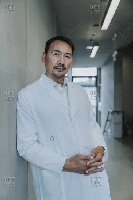 Scientist with hands clasped leaning on wall at clinic corridor