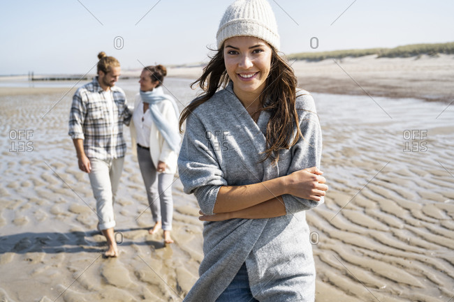 Smiling young woman walking with family in background at beach