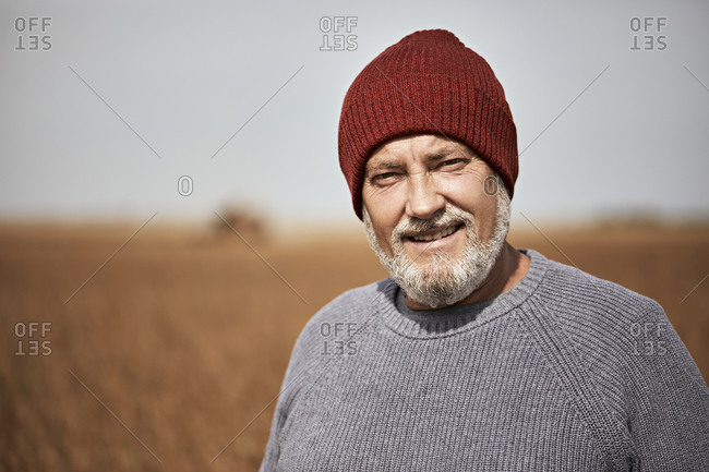 Farmer wearing knit hat smiling while standing at soybean farm