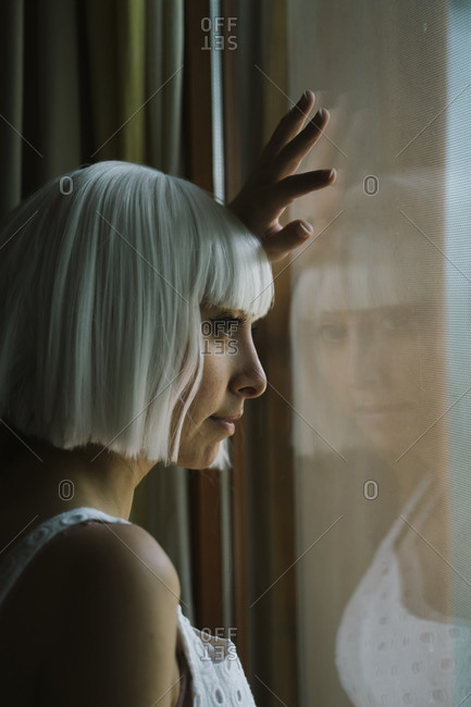 White hair woman looking through window while standing at home