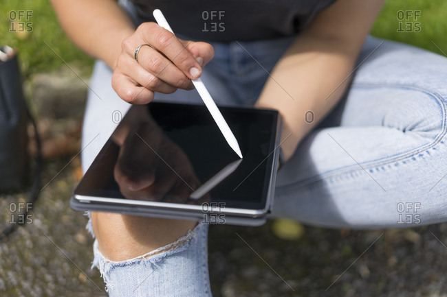 Hands of woman drawing on graphic tablet while sitting in park