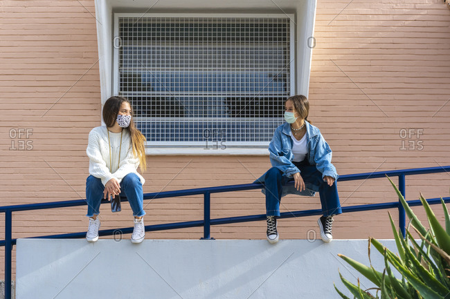Female friends looking at each other while sitting on railing