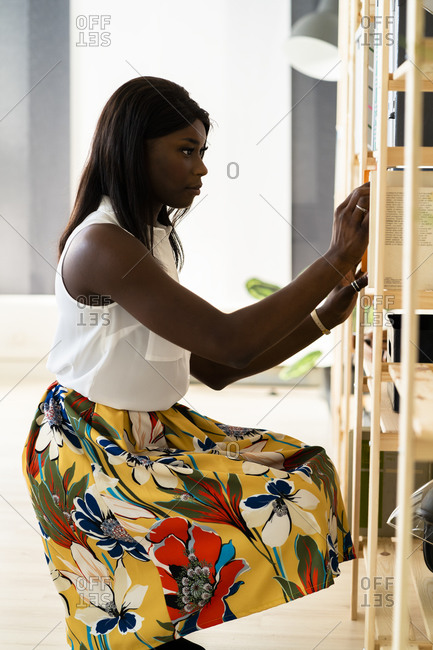 Businesswoman crouching while finding book in shelf at office