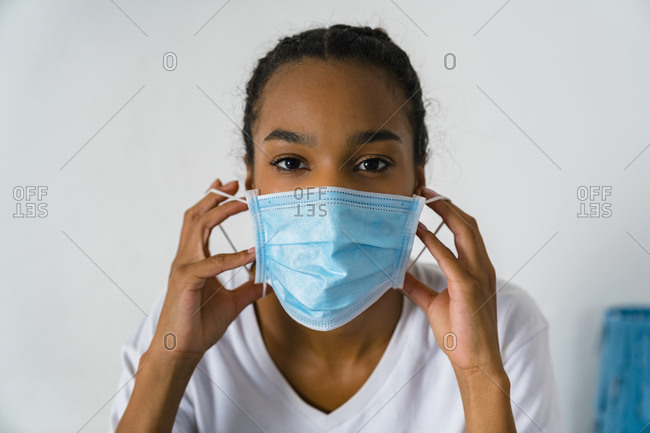 Young girl wearing protective face mask standing against wall