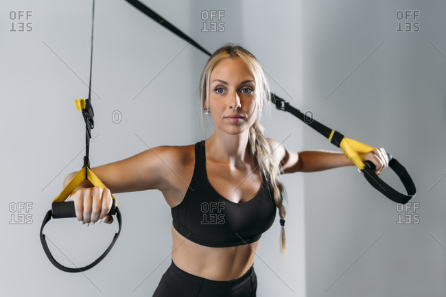 Young female athlete preparing for suspension training in gym