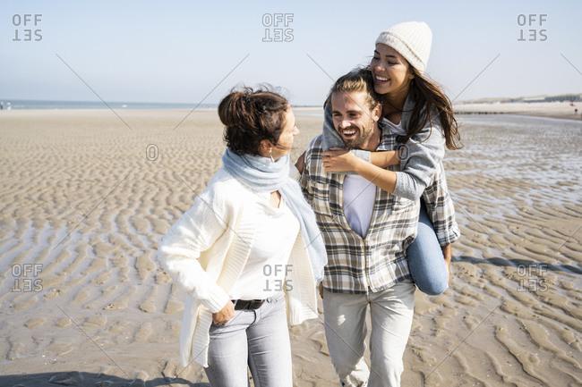 Mature woman looking at daughter piggybacking on man at beach