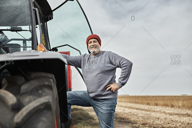Confident farmer standing with hand on hip by tractor at farm