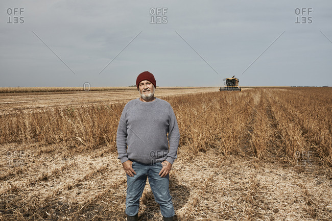 Smiling farmer standing with hands in pockets at soybean farm