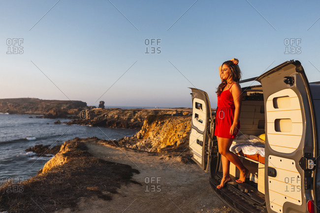 Young woman with hand in hair standing in camper van at beach