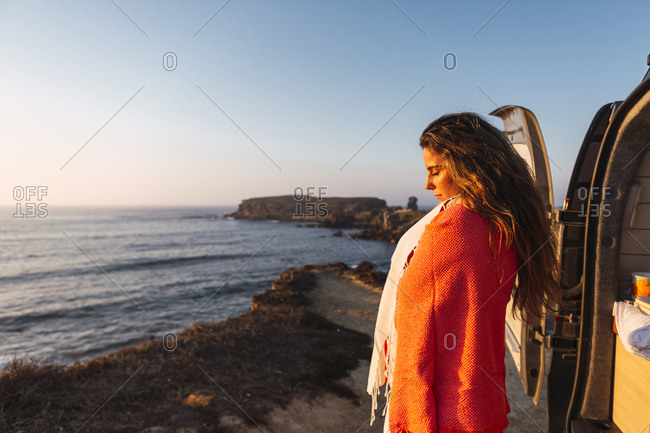 Woman with eyes closed covering shawl while standing at beach