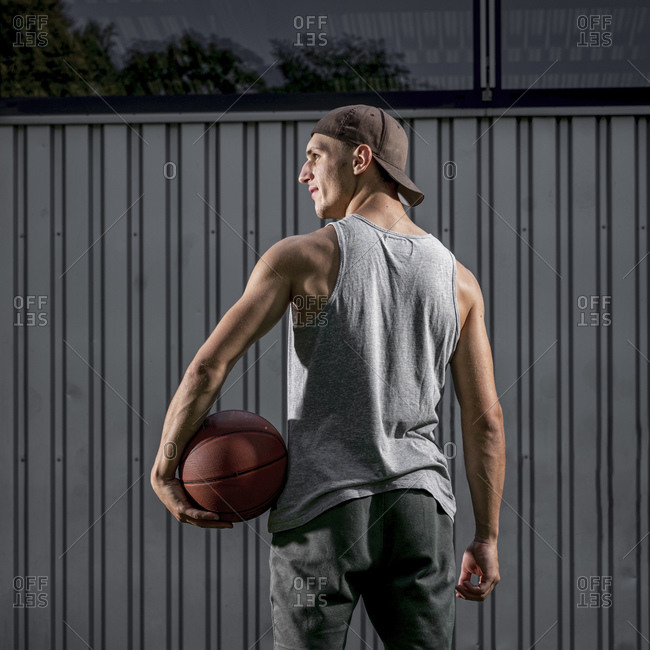 Young man holding ball while looking away at basketball court