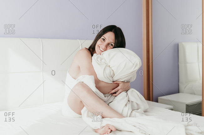 Happy beautiful woman hugging blanket sitting on bed at home