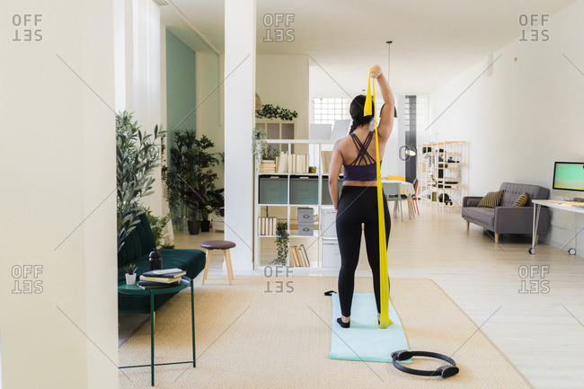 Young woman stretching with resistance band standing at home