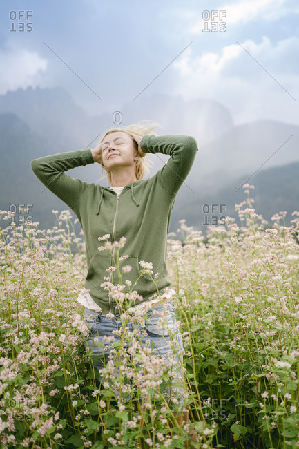 Woman standing with hands behind head amidst plants on field