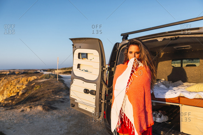 Young woman covered in shawl standing by camper van at beach